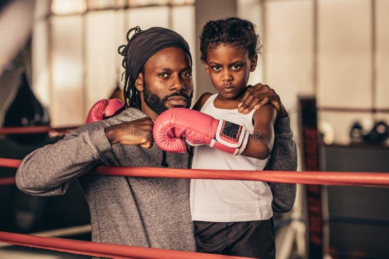 Entraîneur de boxe avec un boxeur d'enfant se tenant à l'intérieur d'un ring image libre de droits
