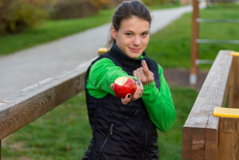 Entraîneur de Fitnes offrant une pomme au gymnase extérieur photo libre de droits