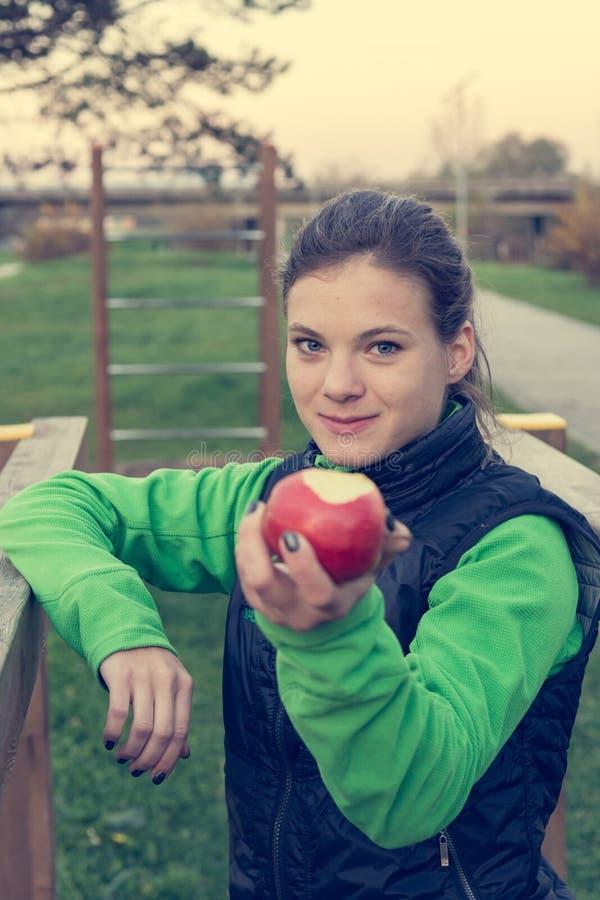 Entraîneur de Fitnes offrant une pomme au gymnase extérieur image libre de droits
