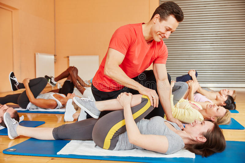 Entraîneur de forme physique aidant avec l'exercice de gymnastique photo libre de droits