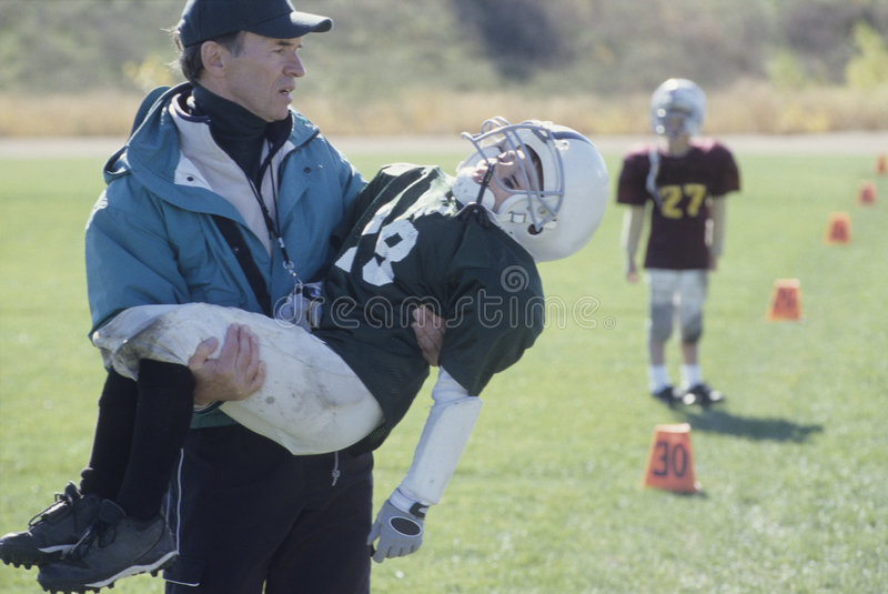 Entraîneur de petite ligue avec le joueur de football blessé images libres de droits