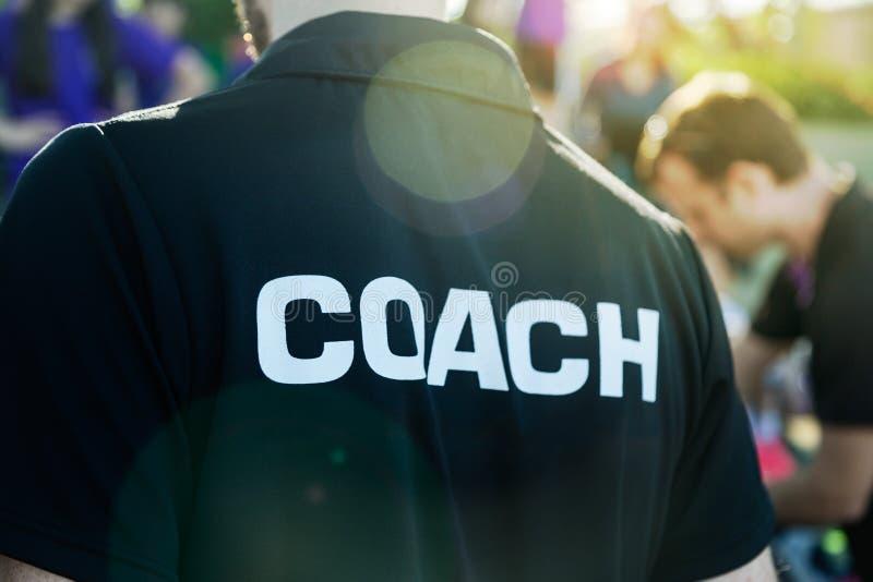 Entraîneur de sport dans la chemise noire avec le texte blanc d'entraîneur sur le sta arrière photographie stock