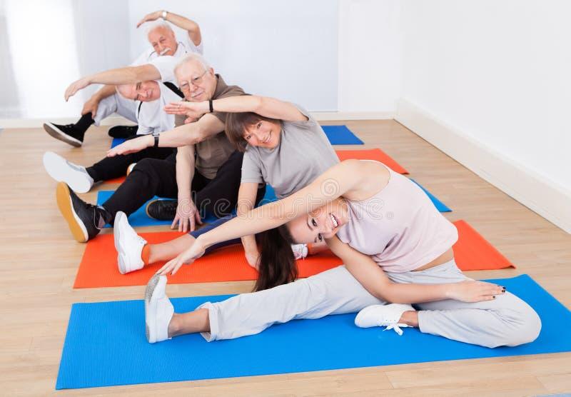 Entraîneur et clients supérieurs faisant le yoga photo stock