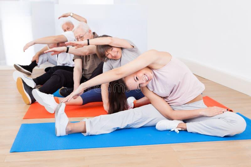 Entraîneur et clients supérieurs faisant le yoga photographie stock