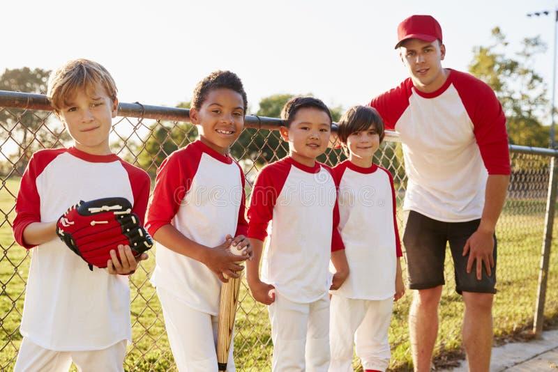 Entraîneur et jeunes garçons dans une équipe de baseball regardant à l'appareil-photo images stock