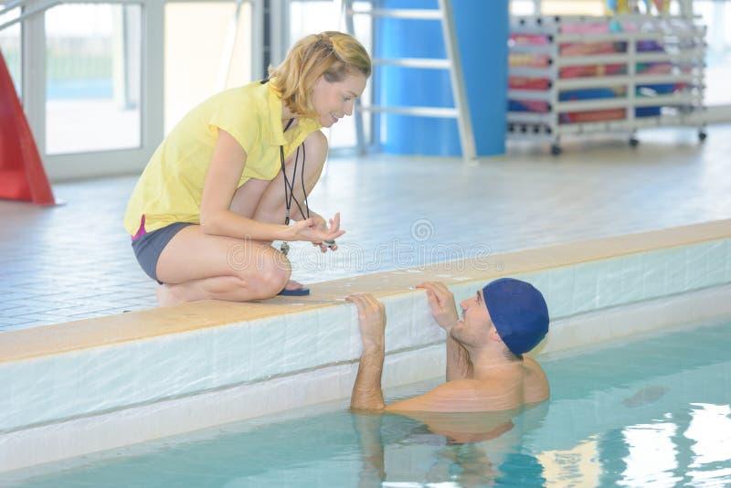 Entraîneur féminin donnant des leçons particulières au nageur au centre de loisirs photographie stock libre de droits