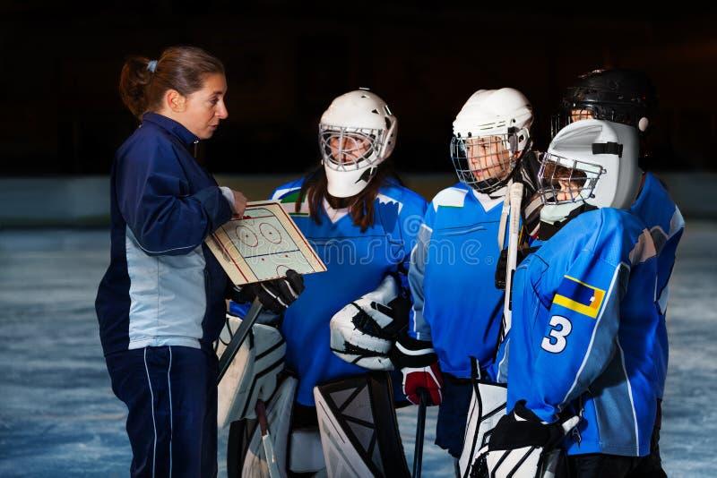 Entraîneur féminin expliquant la stratégie à l'équipe de hockey photo libre de droits