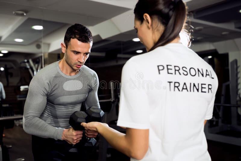 Entraîneur féminin faisant la séance d'entraînement avec son client photographie stock