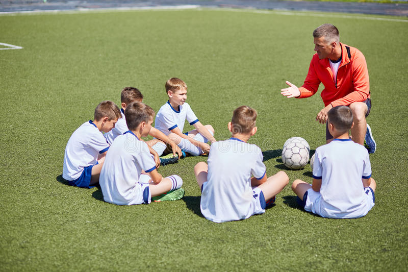 Entraîneur Instructing Football Team dans le domaine image stock