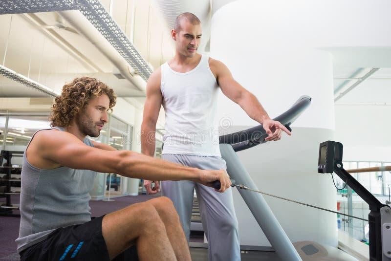 Entraîneur masculin aidant l'homme sur la machine de forme physique au gymnase photos stock