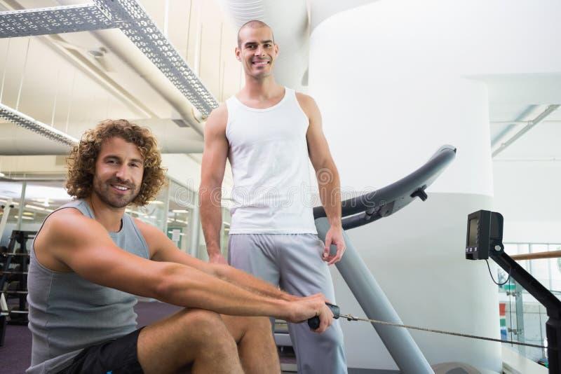Entraîneur masculin aidant l'homme sur la machine de forme physique au gymnase photographie stock