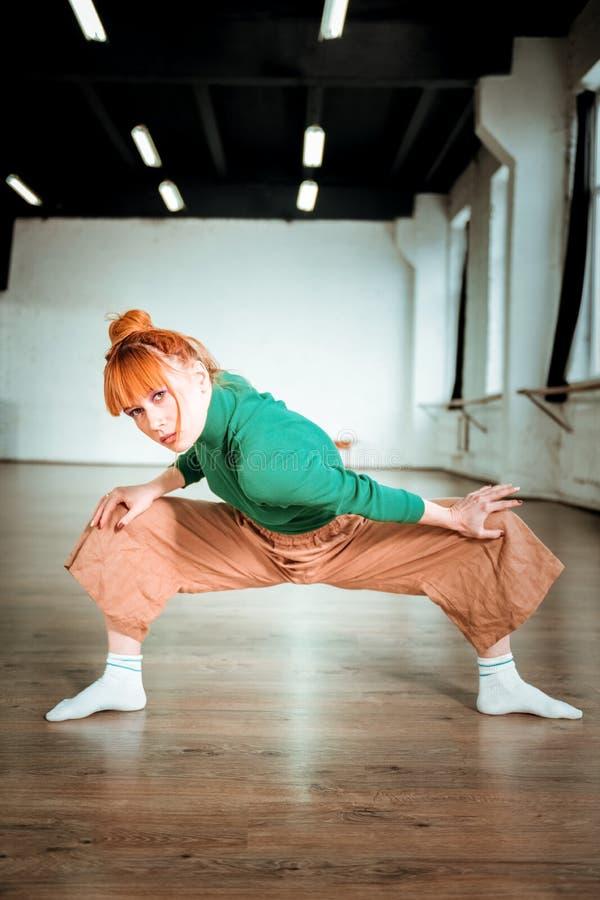 Entraîneur mince beau de yoga dans un col roulé vert semblant focalisé photo stock