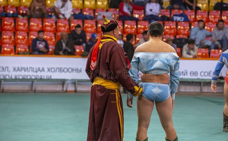 Entraîneur mongol pinçant un bon à rien d'un lutteur pour la bonne chance image libre de droits