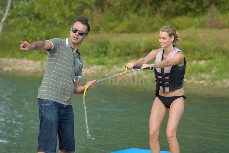 Entraîneur montrant quelque chose à l'interprète de ski d'eau photo stock