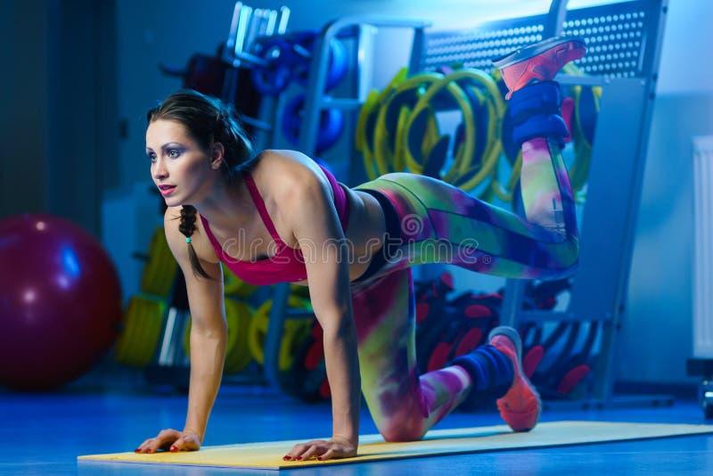 Entraîneur musculaire attirant puissant W de forme physique de femme orking  photographie stock libre de droits