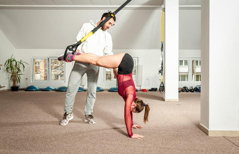 Entraîneur personnel masculin bel avec une barbe aidant la jeune belle fille pour l'exercice d'aérobic dans le gymnase, vrai peo  photos stock