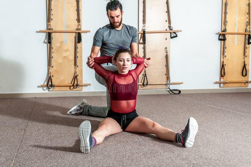 Entraîneur personnel masculin de yoga beau avec une barbe aidant la jeune fille de forme physique à étirer ses muscles après séan image stock