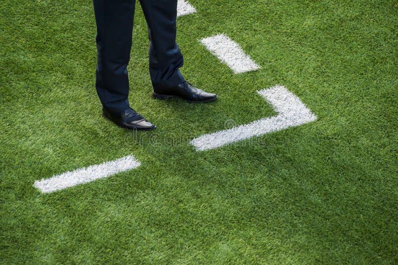 Entraîneur se tenant à côté de la ligne de craie sur le terrain de football photos libres de droits