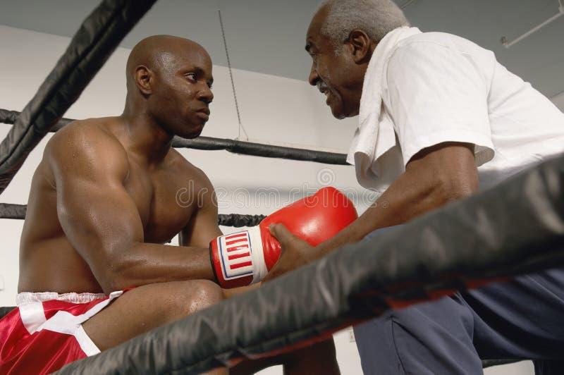 Entraîneur supérieur conseillant au boxeur photos libres de droits