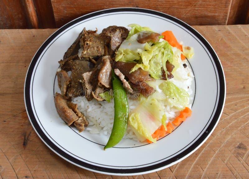 Entrañas fritas del cerdo con ajo y la verdura mezclada sofrita en el arroz imagen de archivo libre de regalías
