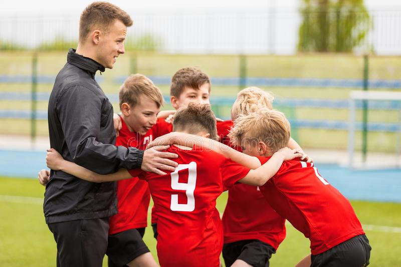 Entra?nement des sports de la jeunesse Le football Team Huddle du football d'enfants avec l'entraîneur images libres de droits