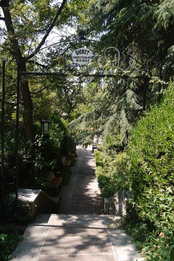 Entrada al callejón a través del parque al cuarto de bomba con agua mineral para la salud del organismo fotografía de archivo