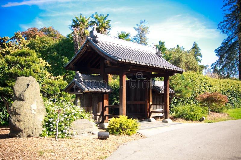 A entrada ao céu azul do jardim japonês nubla-se árvores imagens de stock