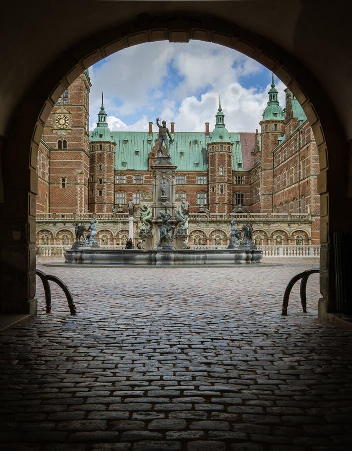 Entrada através de uma porta escura sob um arco ao molde de Frederiksborg fotografia de stock royalty free