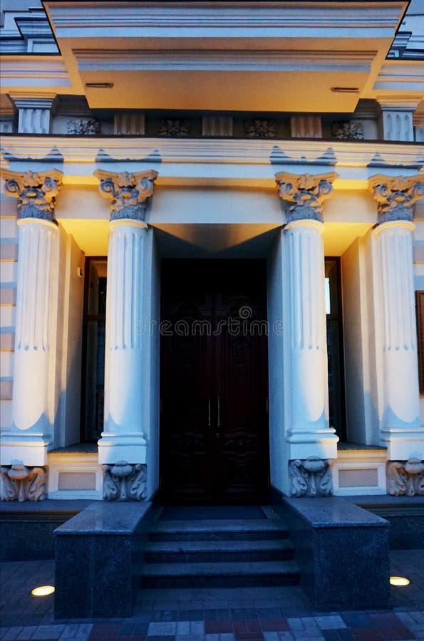 Entrada bonita à construção com colunas e luzes da noite imagens de stock royalty free