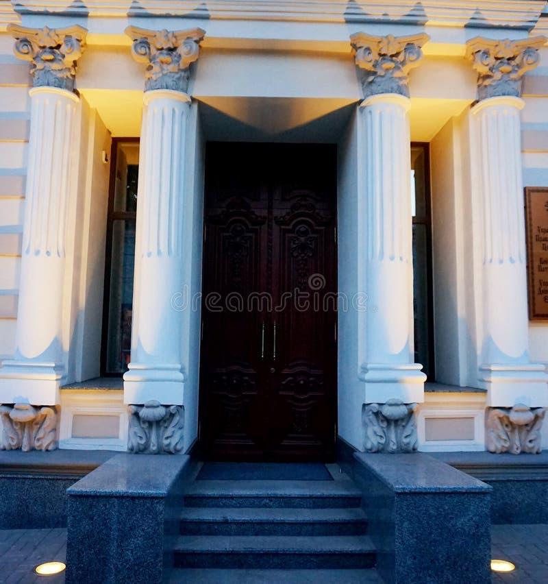 Entrada bonita à construção com colunas e luzes da noite imagens de stock