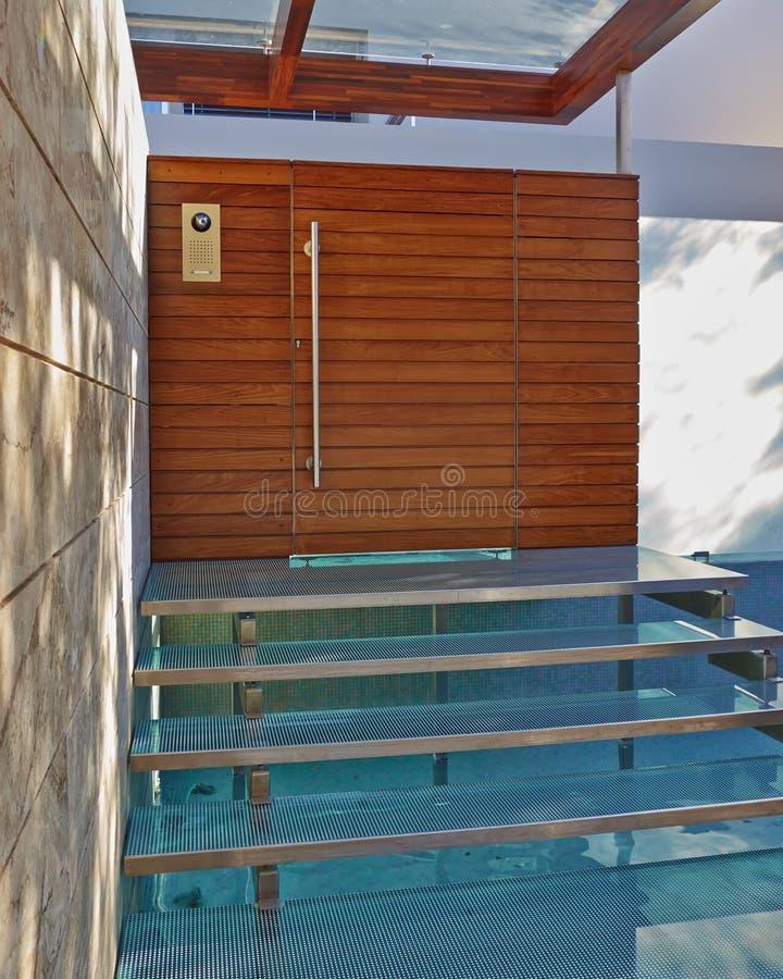 Entrada contemporánea de la casa con la piscina de agua fotografía de archivo libre de regalías