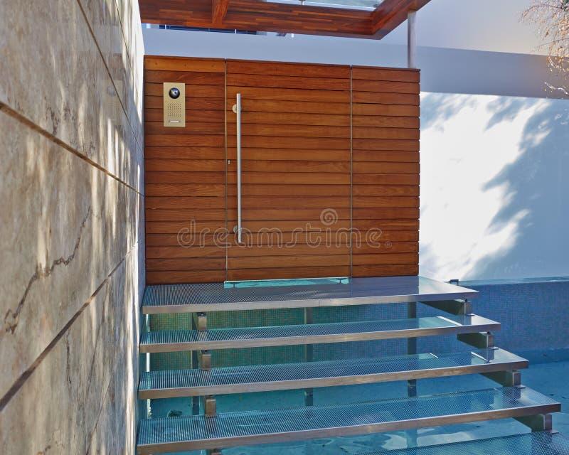 Entrada contemporánea de la casa con la piscina de agua fotos de archivo