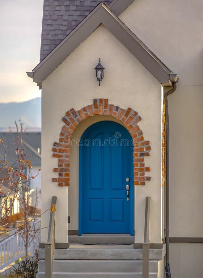 Entrada da casa com escadas e a porta azul arqueada imagem de stock royalty free