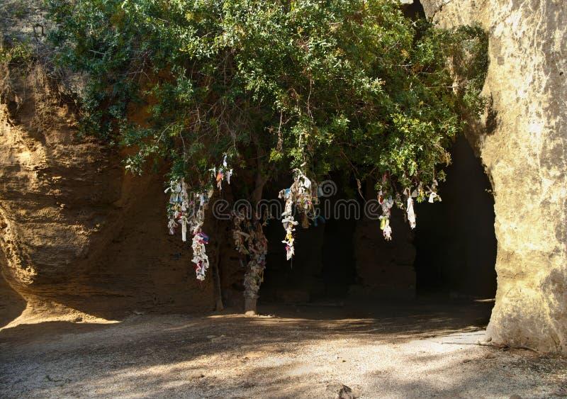 Entrada da catacumba com árvore e partes de pano amarradas imagens de stock