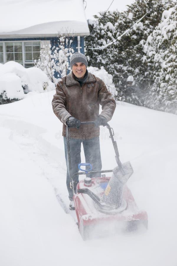 Entrada de automóveis do esclarecimento do homem com snowblower imagens de stock royalty free
