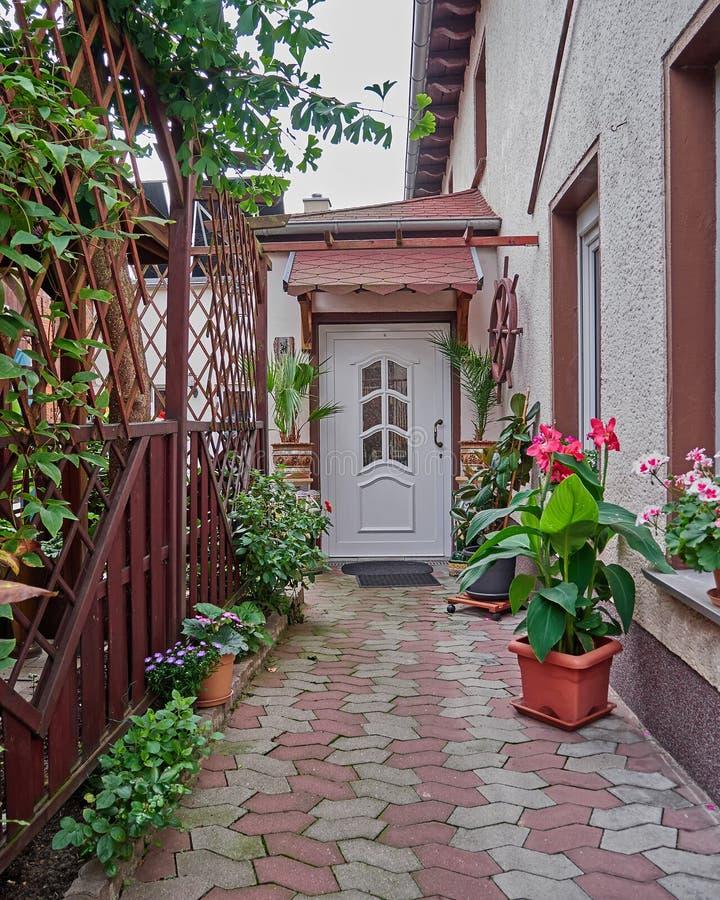 Entrada de la casa con las flores y las plantas fotos de archivo