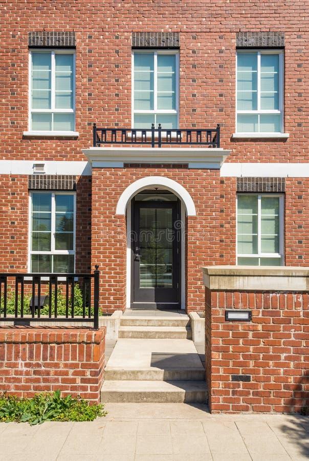 Entrada de la nueva construcción de viviendas con pasos concretos y cerca del ladrillo en frente fotografía de archivo