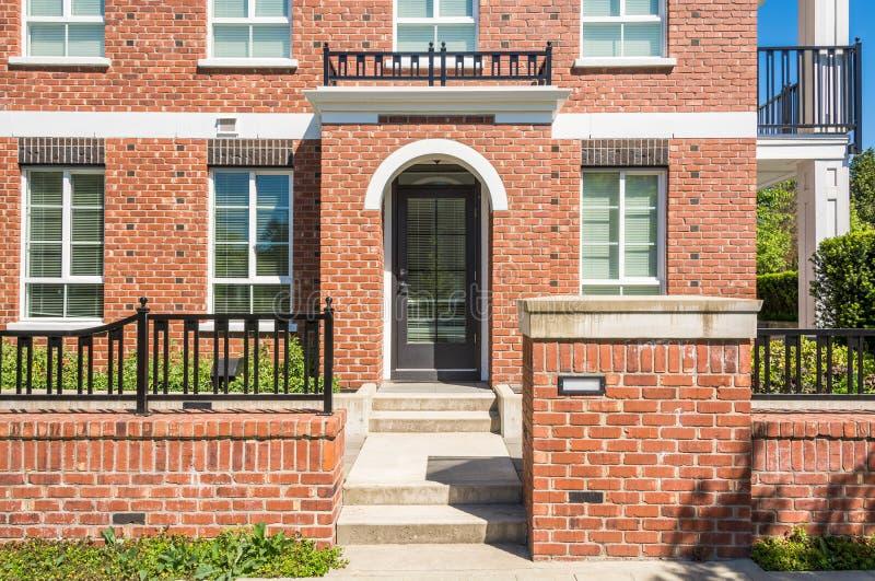Entrada de la nueva construcción de viviendas con pasos concretos y cerca del ladrillo en frente imagen de archivo libre de regalías
