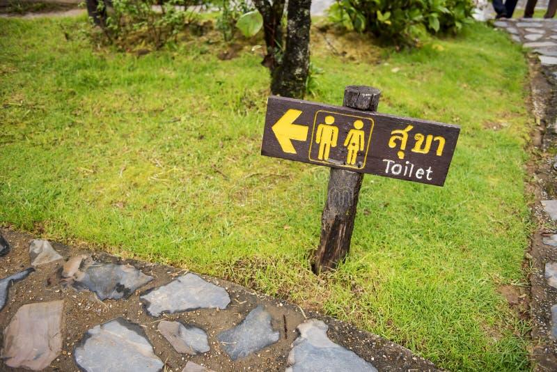 Entrada de madeira do sinal ao toalete em línguas tailandesas e inglesas imagem de stock royalty free
