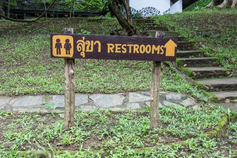 Entrada de madeira do sinal ao toalete em línguas tailandesas e inglesas fotografia de stock royalty free