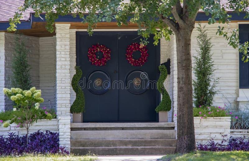 Entrada de una casa de piedra blanca exclusiva con las puertas asiáticas del estilo con las manijas grandes de la ronda y el land foto de archivo libre de regalías