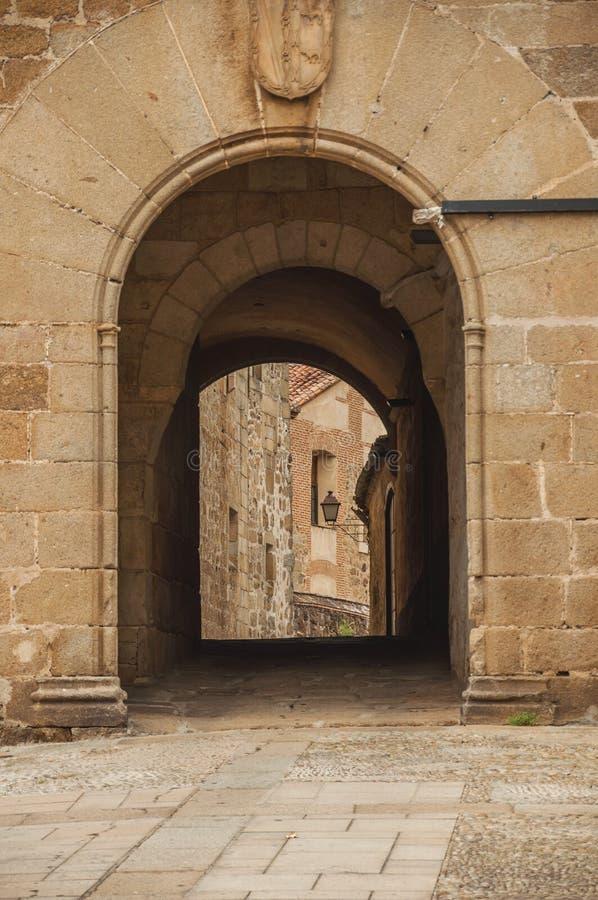 Entrada del arco que pasa a un callejón entre los edificios de piedra góticos en Plasencia imagen de archivo libre de regalías