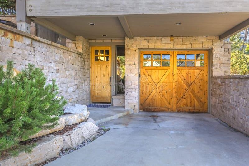 Entrada del garaje con el ladrillo de piedra y las puertas de madera fotos de archivo