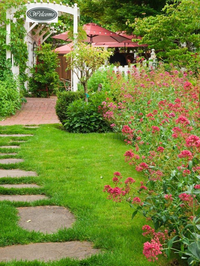 Entrada del jardín con el camino y las flores imágenes de archivo libres de regalías