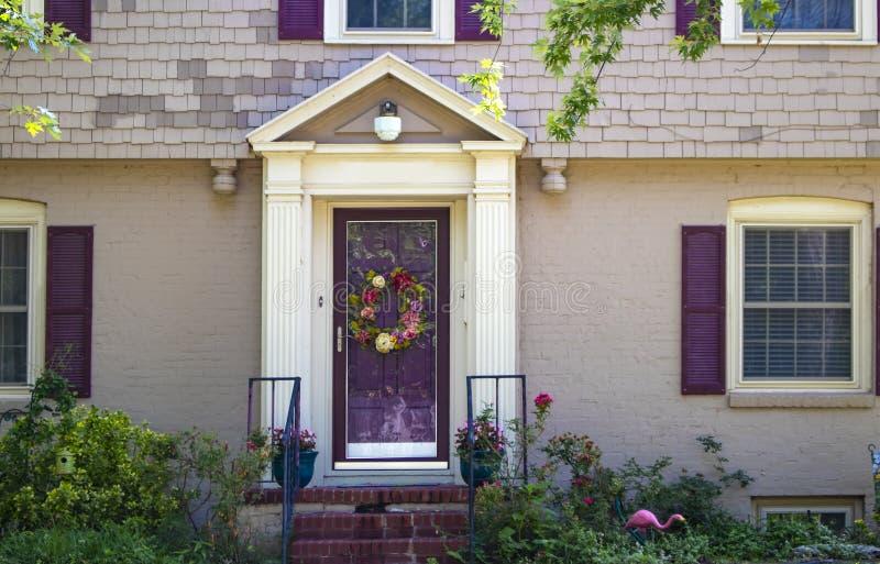Entrada e porta da rua da casa de campo pintada beauitufl do tijolo e da telha com obturadores roxos e triming e grinalda e rosas imagens de stock royalty free