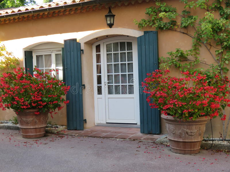 Entrada francesa de la cabaña con verdor y flores rojas fotos de archivo libres de regalías