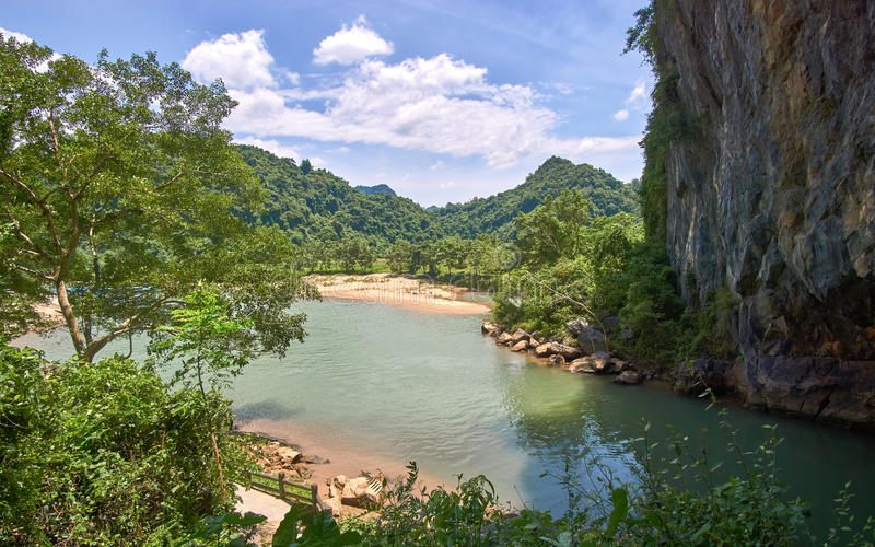 Entrada a la cueva de Phong Nha con claro un río en la cueva y las montañas en el fondo Phong Nha KE golpea la región imágenes de archivo libres de regalías