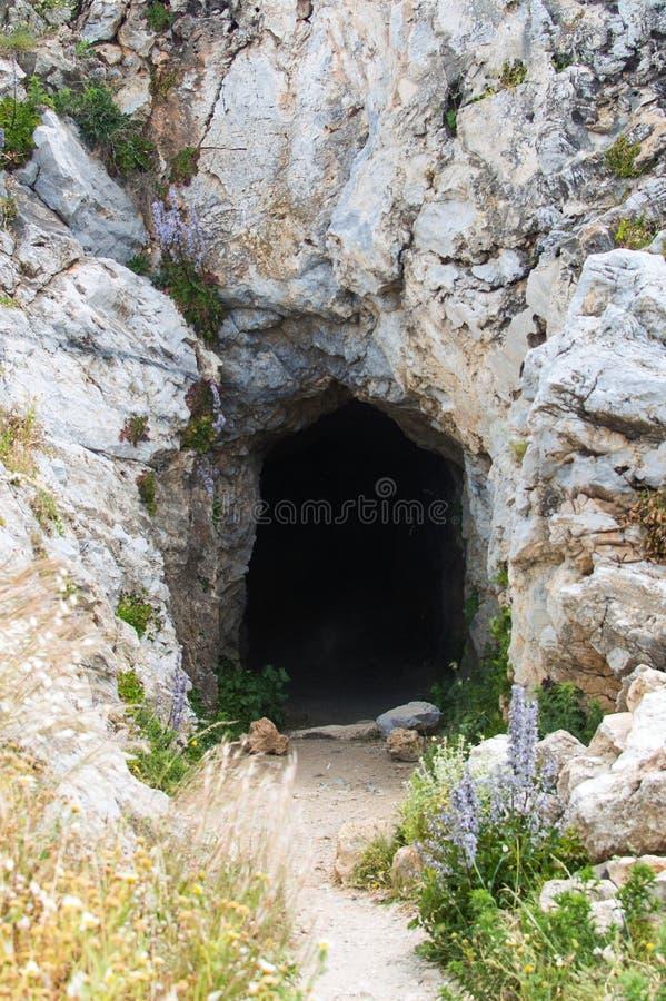 Entrada a la cueva en rocas del acantilado Concepto del peligro de la exploración del viaje fotos de archivo