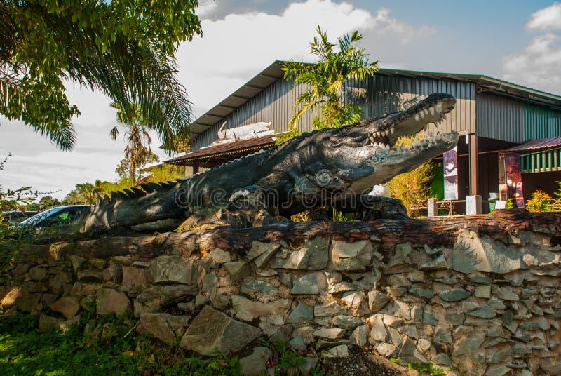 Entrada a la granja, un cocodrilo relleno sarawak borneo malasia imagenes de archivo