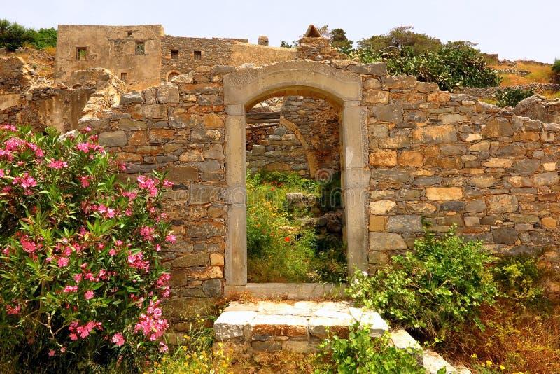 Entrada a las ruinas con los wildflowers, isla de Spinalonga, Creta, Grecia imagen de archivo libre de regalías